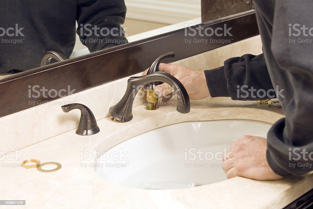 Plumber Installing New Bathroom Faucet stock photo