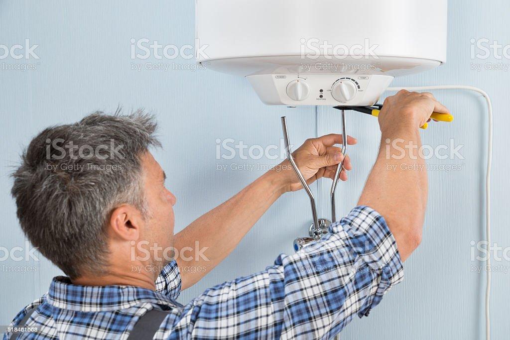 Plumber Installing Water Heater stock photo