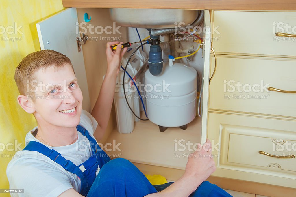 Plumber installs a water filter. water filter. stock photo