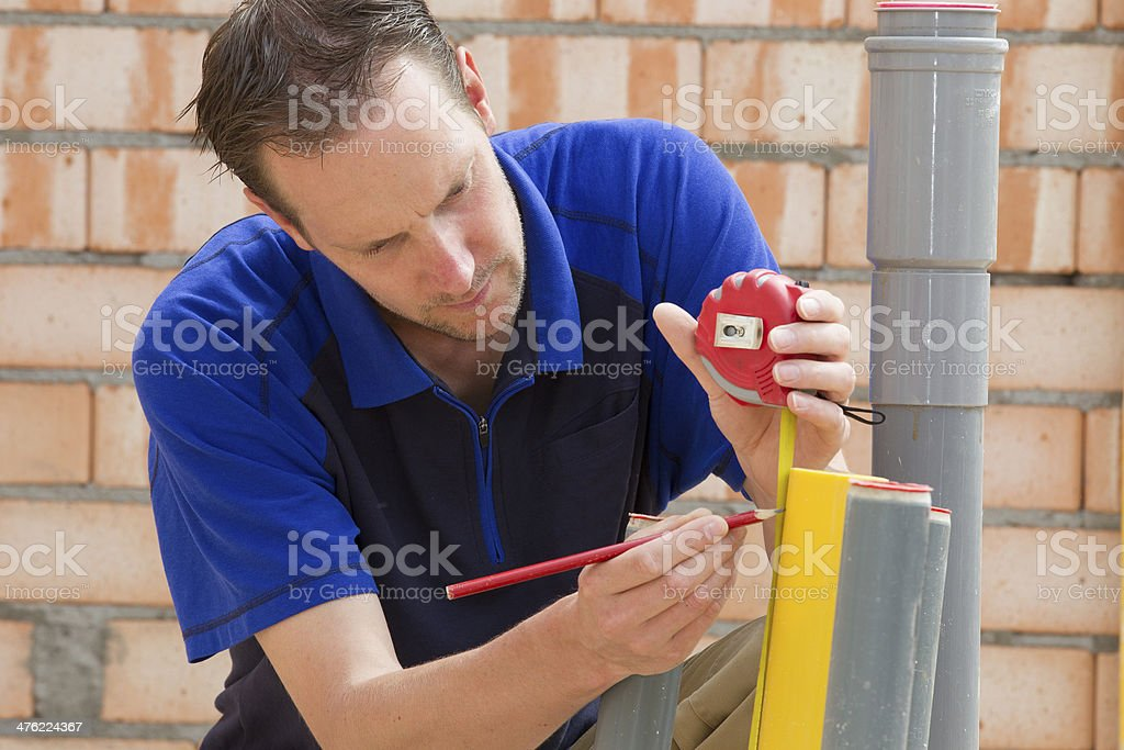 Plumber looking at pipe royalty-free stock photo