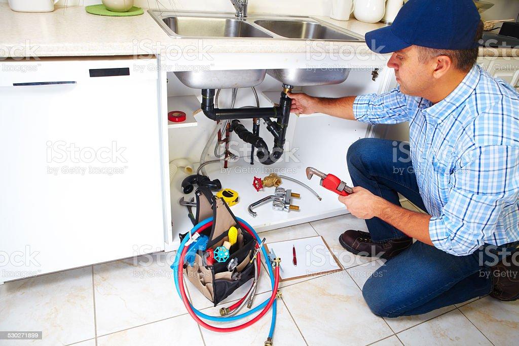 Plumber on the kitchen. stock photo