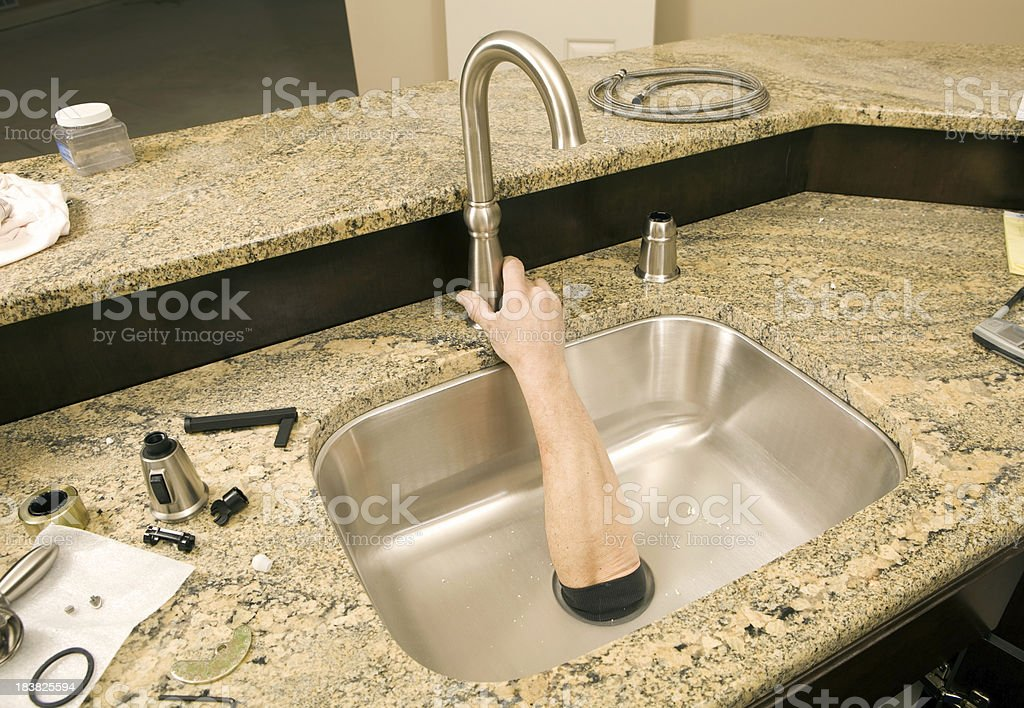 Plumber Reaches Hand through Sink Drain to Attach Faucet royalty-free stock photo