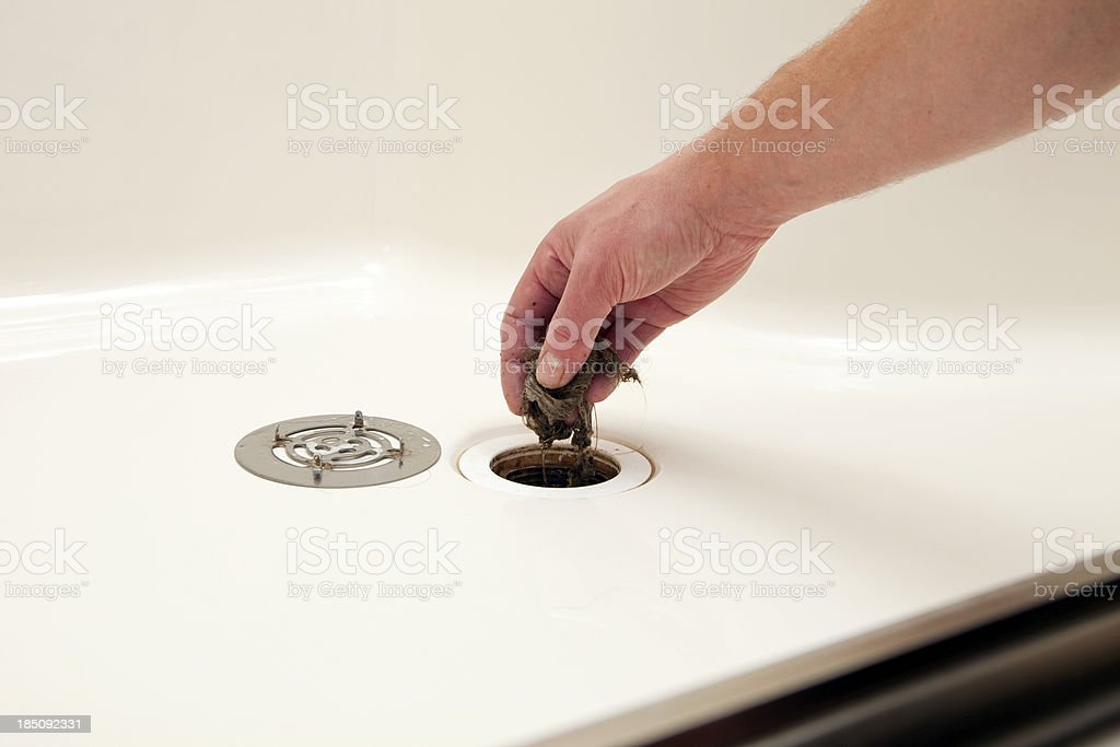 Plumber Removing Hair Clog from Shower Drain stock photo