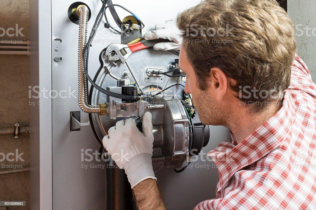 plumber repairing a condensing boiler in the boiler room stock photo