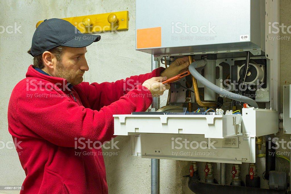 plumber repairing a condensing boiler stock photo