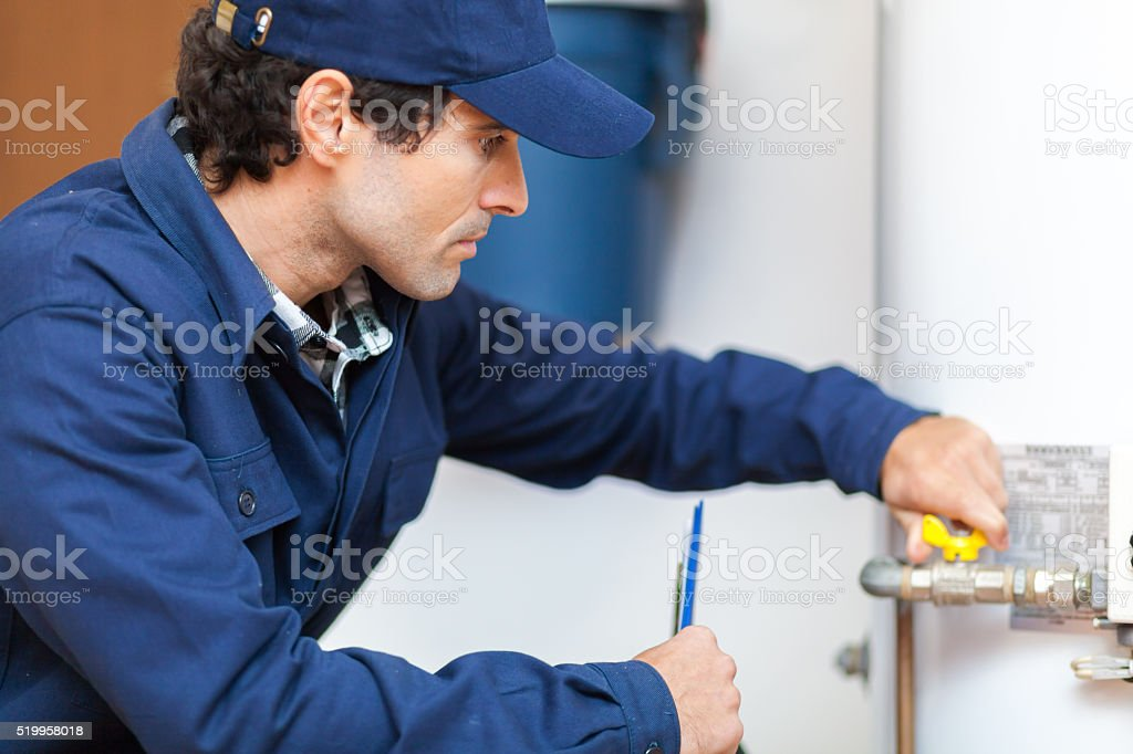 Plumber repairing an hot-water heater stock photo