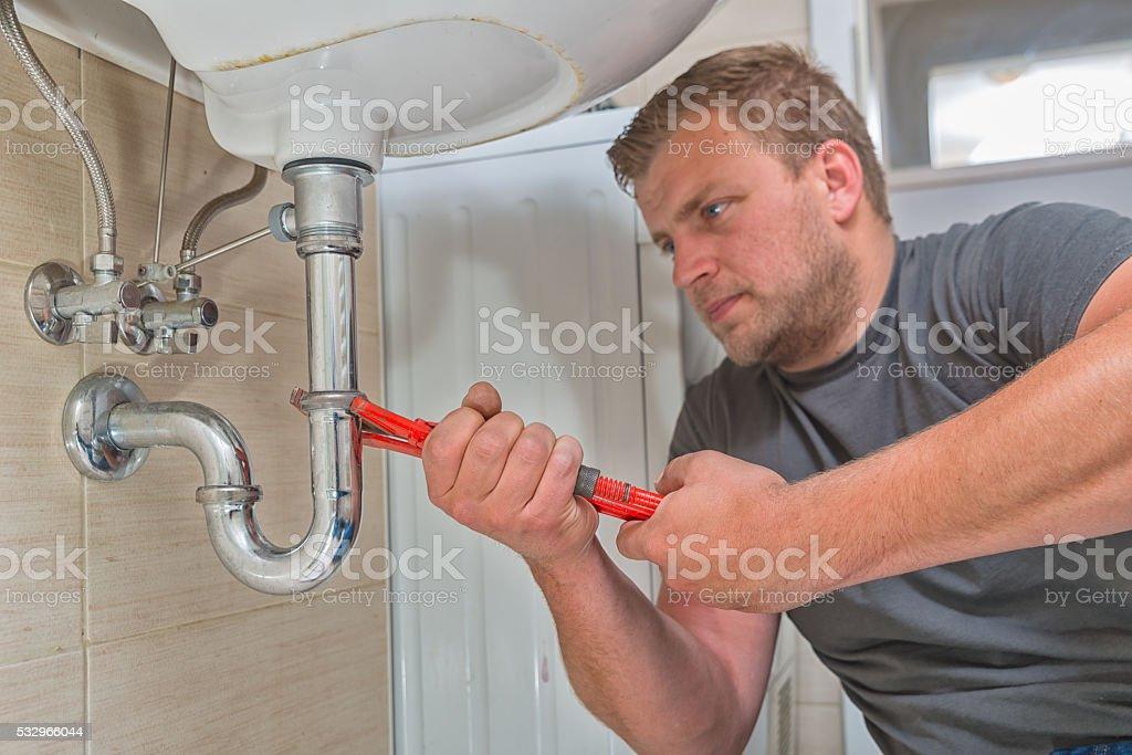 Plumber repairing drain stock photo