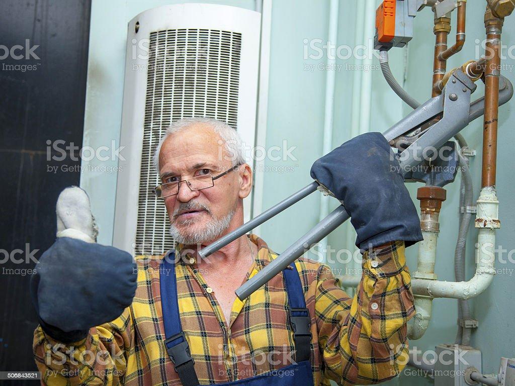Plumber repairing pipes stock photo