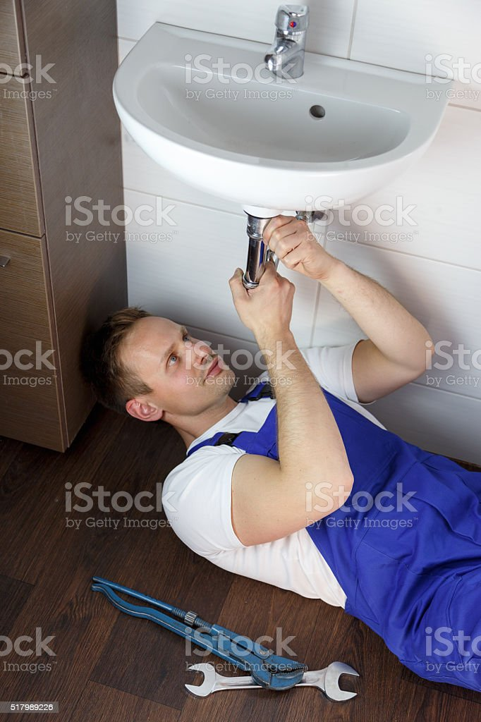 Plumber Repairing Sink In Bathroom stock photo
