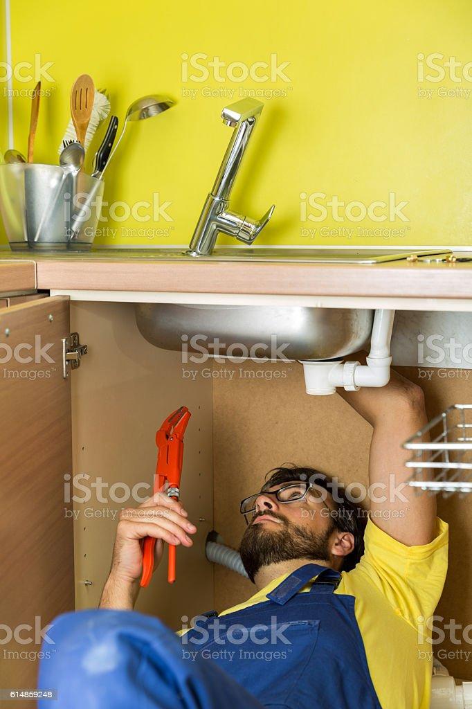 plumber repairing water faucet under kitchen sink