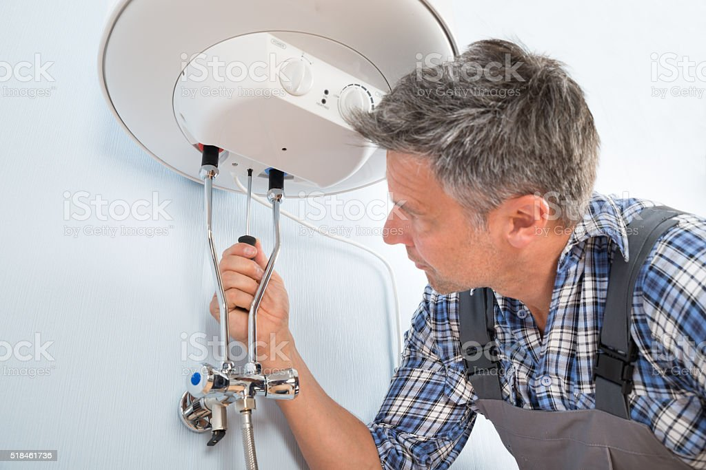 Plumber Repairing Water Heater stock photo