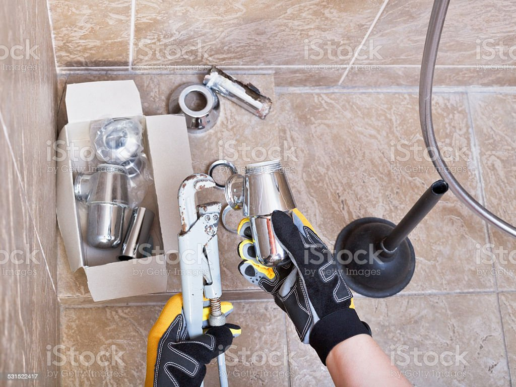 plumber repairs sink trap in bathroom stock photo