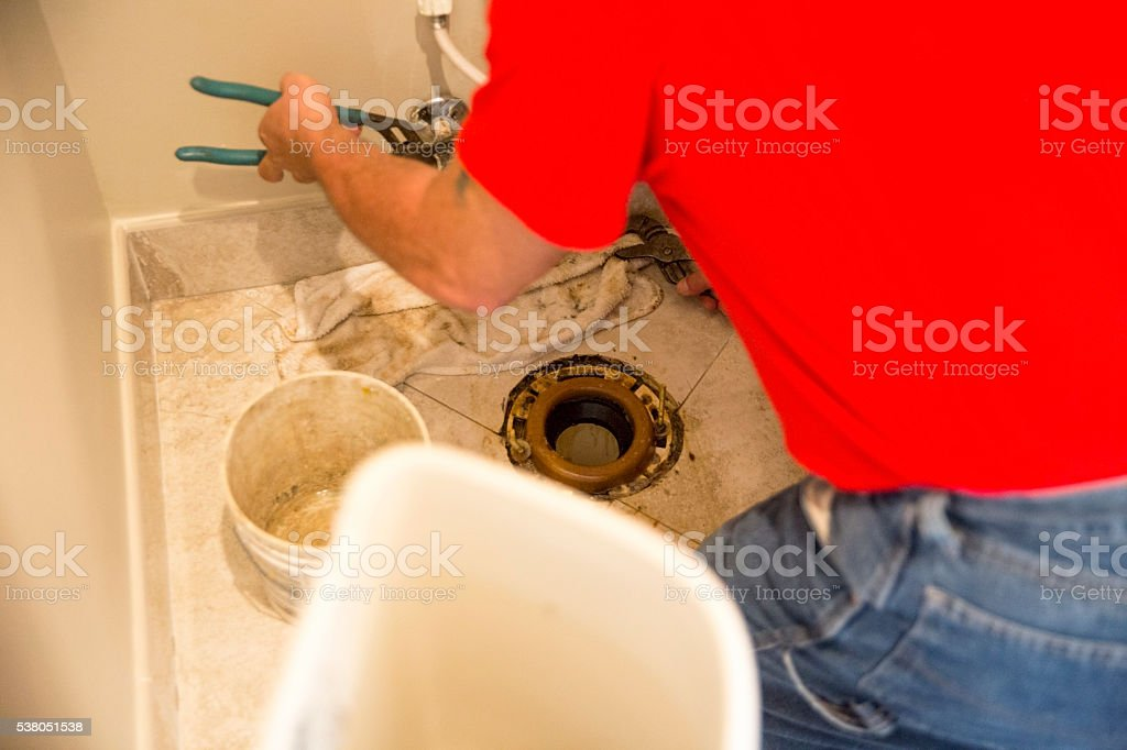 Plumber replacing toilet flange in a home stock photo