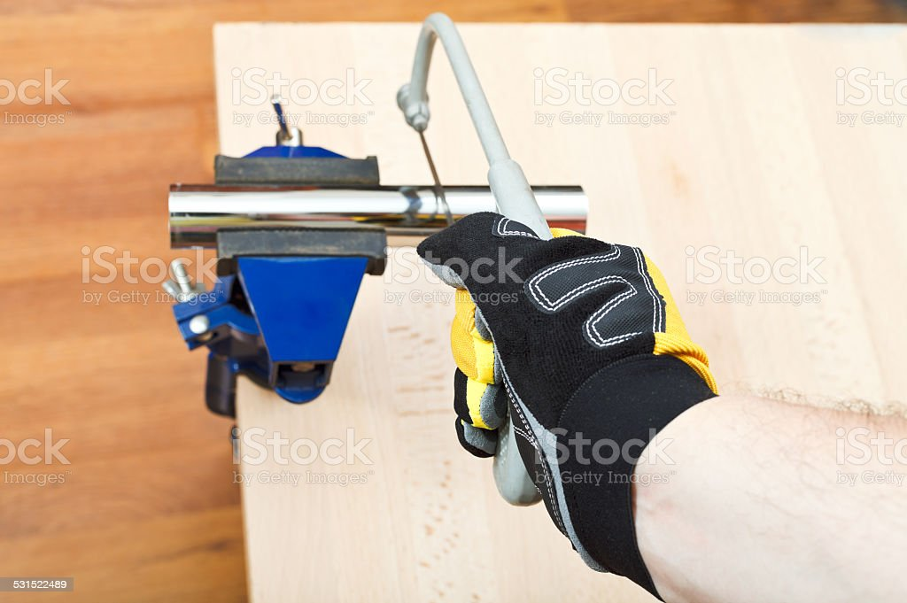 plumber sawing plumbing drain pipe gripped in vice stock photo
