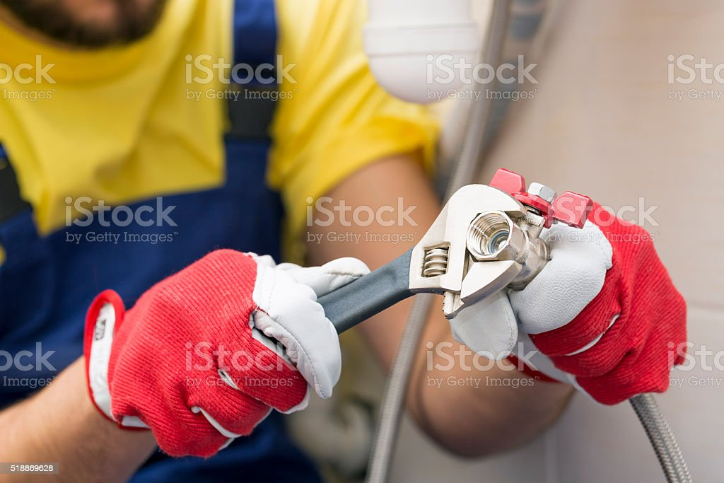 plumber screwing plumbing fittings in bathroom stock photo