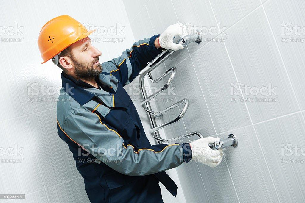 Plumber service. worker installing towel warmer stock photo