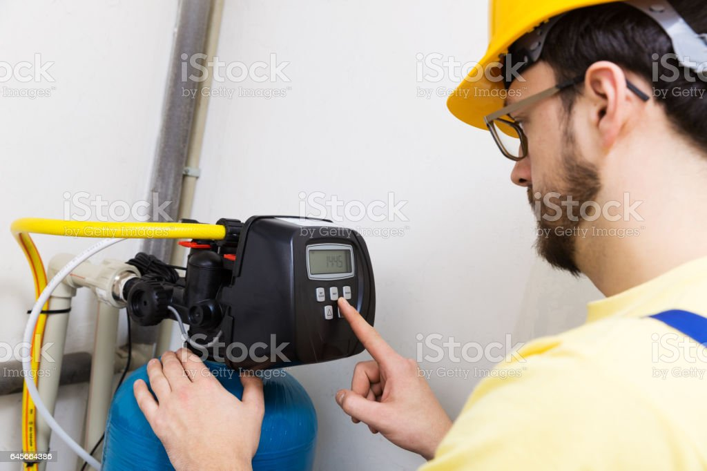 plumber set up water filtration system stock photo