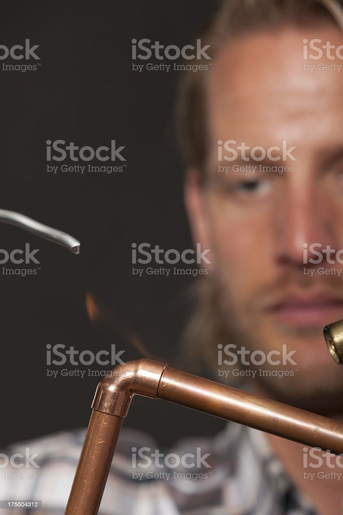 Plumber soldering a copper pipe stock photo