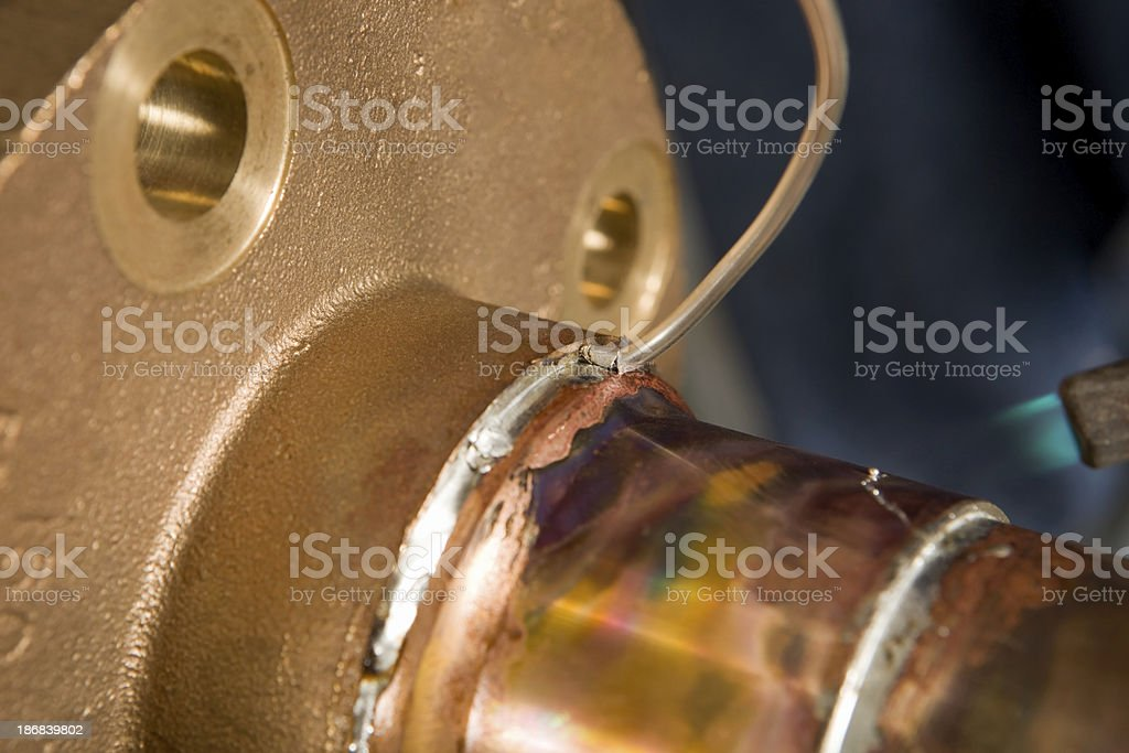 Plumber Sweating a Brass Flange to Copper Pipe royalty-free stock photo