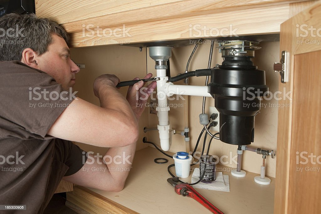 Plumber Using Adjustable Pliers on Sink Drain stock photo