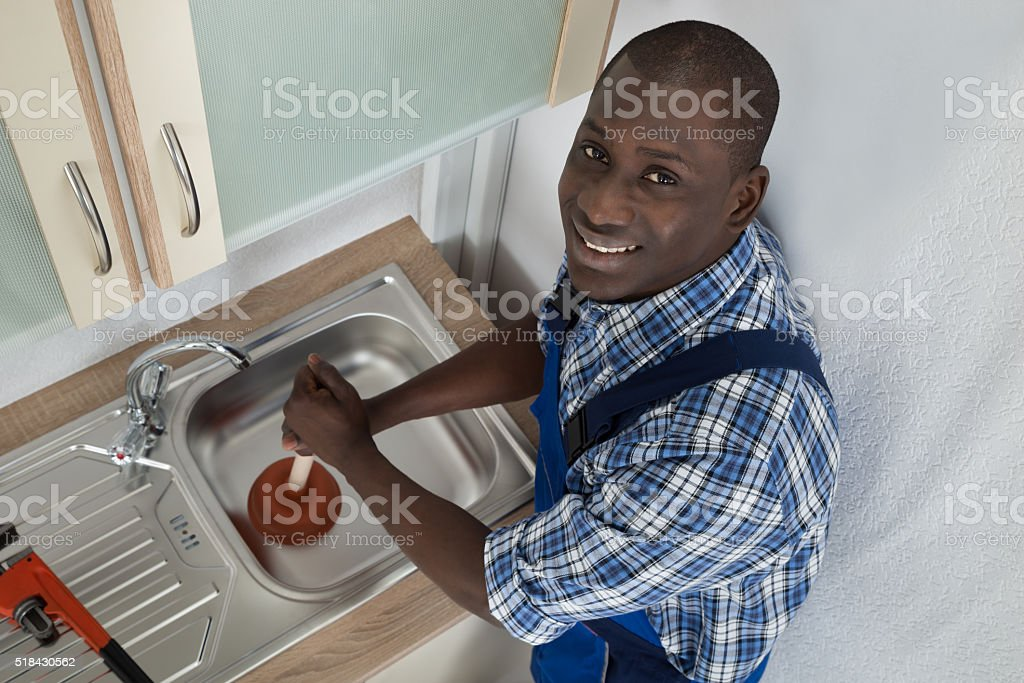 Plumber Using Plunger In Kitchen Sink stock photo