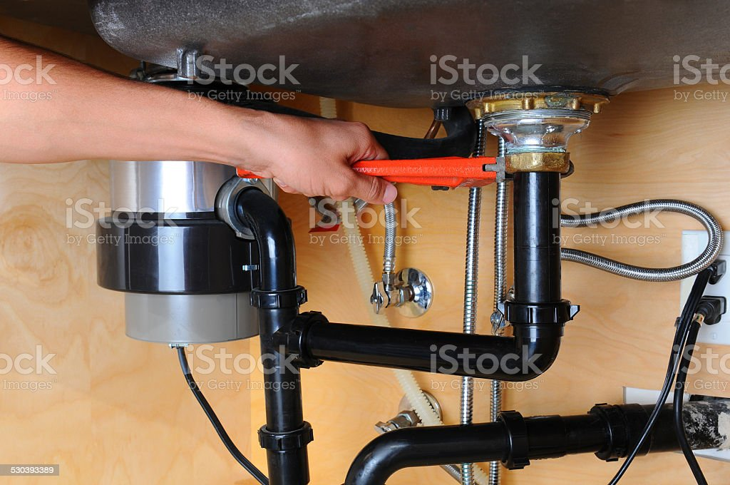 Plumber Using Wrench Under Kitchen Sink stock photo