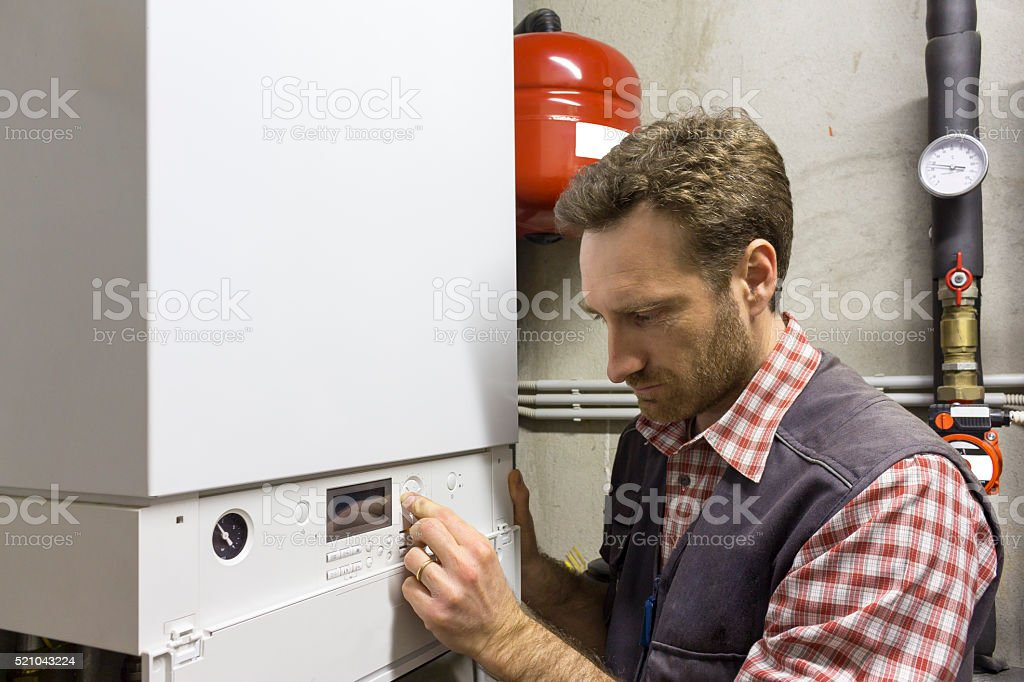plumber who carries out the maintenance of a condensing boiler stock photo