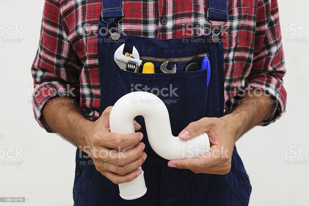 Plumber with plastic u-bend pipe and tools royalty-free stock photo