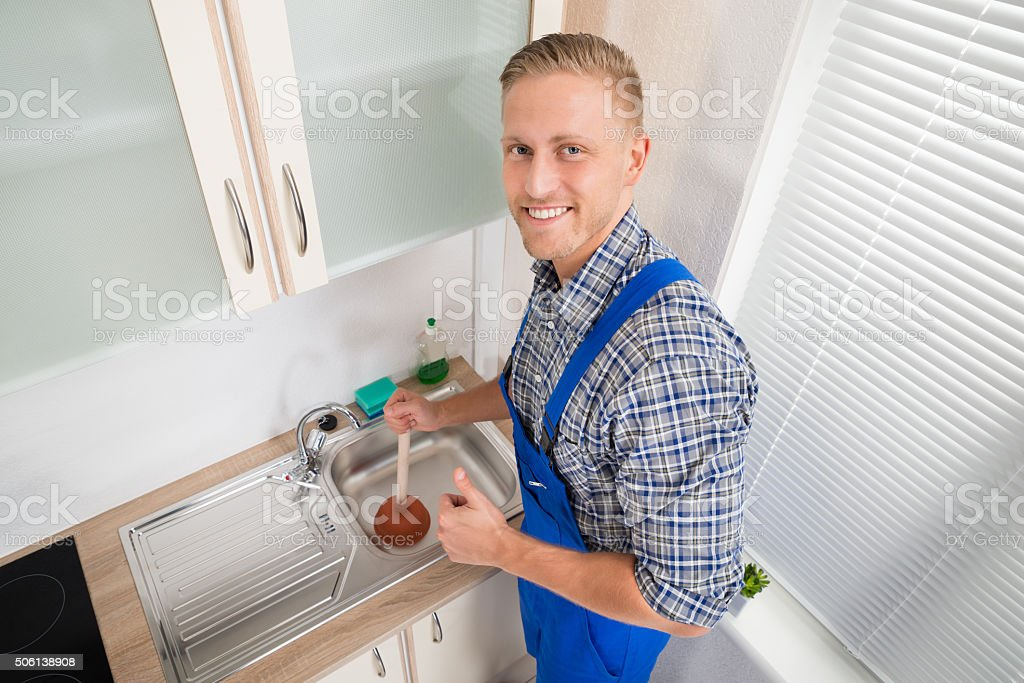 Plumber With Plunger In Kitchen stock photo