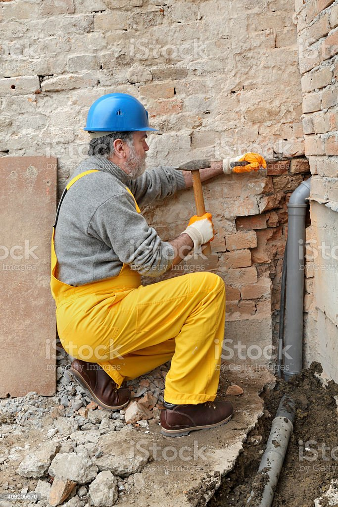 A plumber with yellow pants installing pipes for a building stock photo