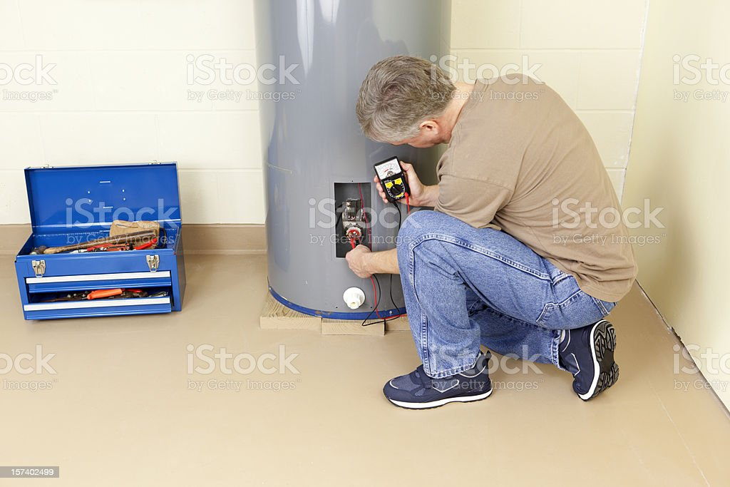 A plumber working in a water heater stock photo