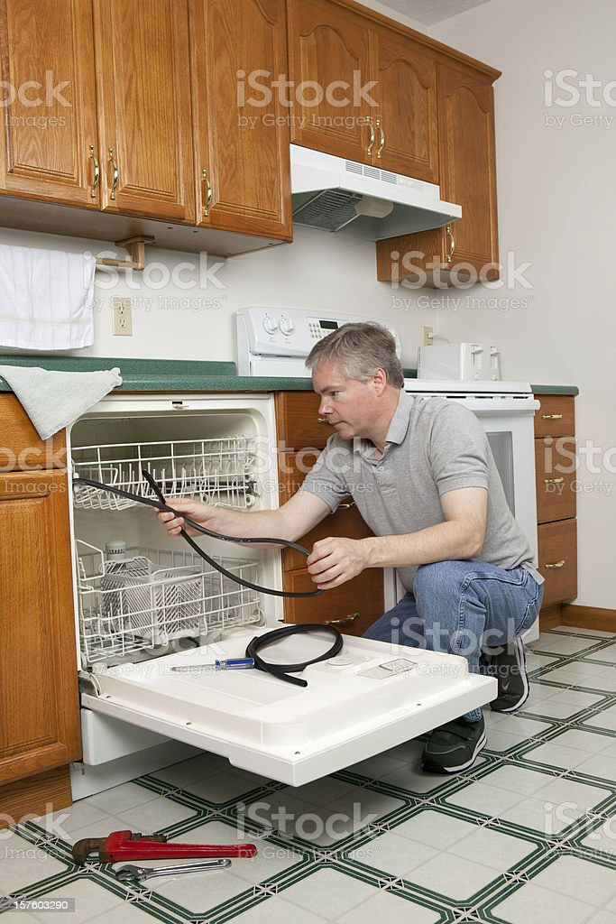 Plumber Working on Dishwasher royalty-free stock photo