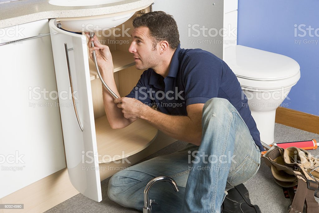 Plumber working on sink royalty-free stock photo