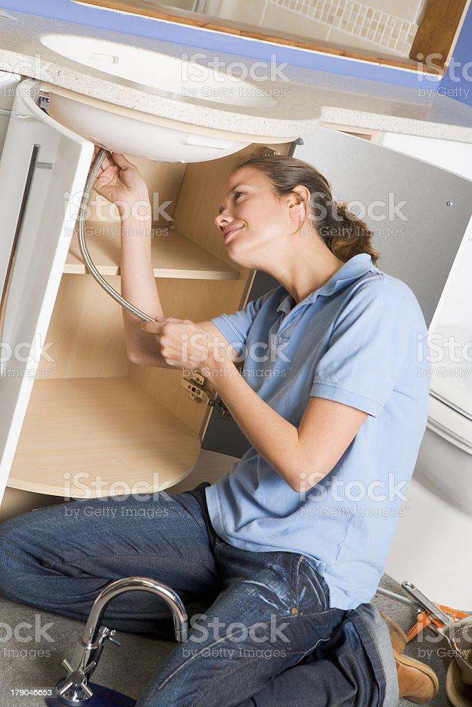 Plumber working on sink smiling royalty-free stock photo