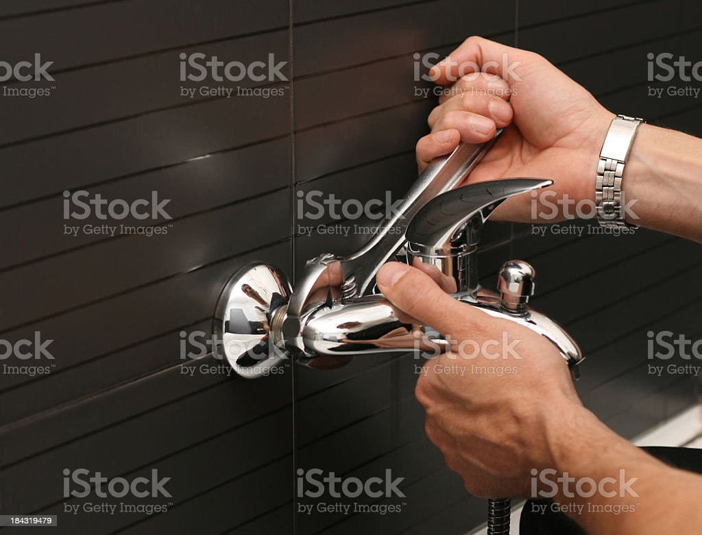 Plumber working with a wrench on a silver faucet royalty-free stock photo