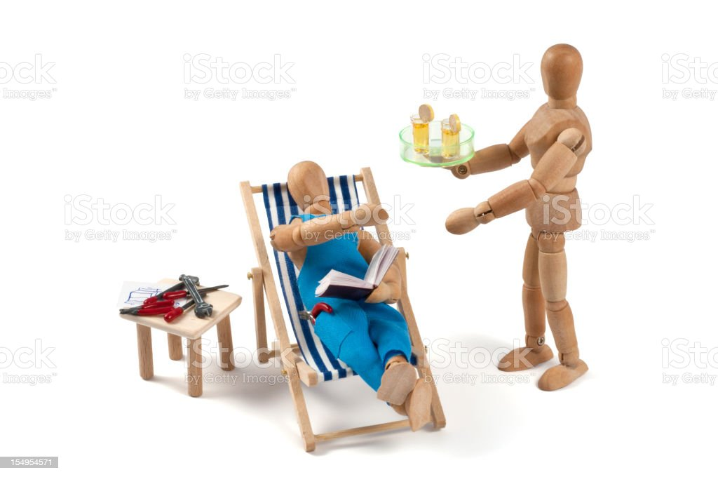 Plumbers dream - wooden mannequin in deckchair with waitress stock photo