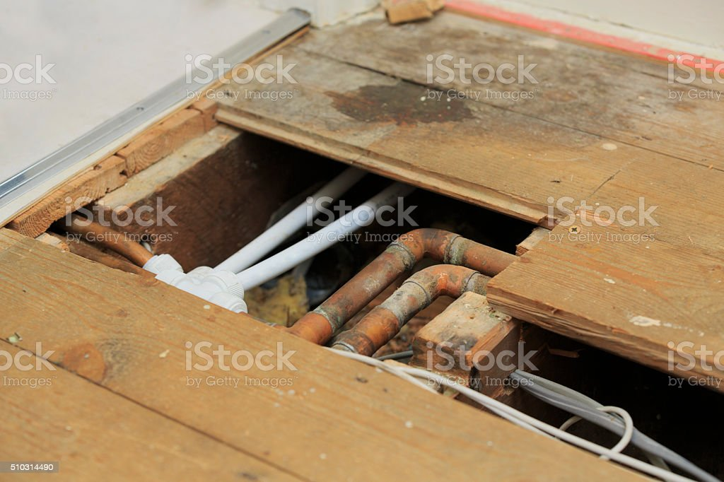 Plumbing and pipework under old floorboards stock photo