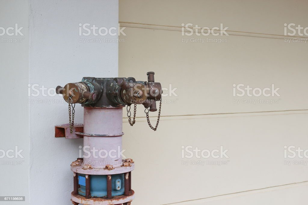 plumbing fire hydrant in a metal line wall, fireplug with valves stock photo