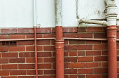 Plumbing Pipes on Cracked Blue and Red Brick Wall