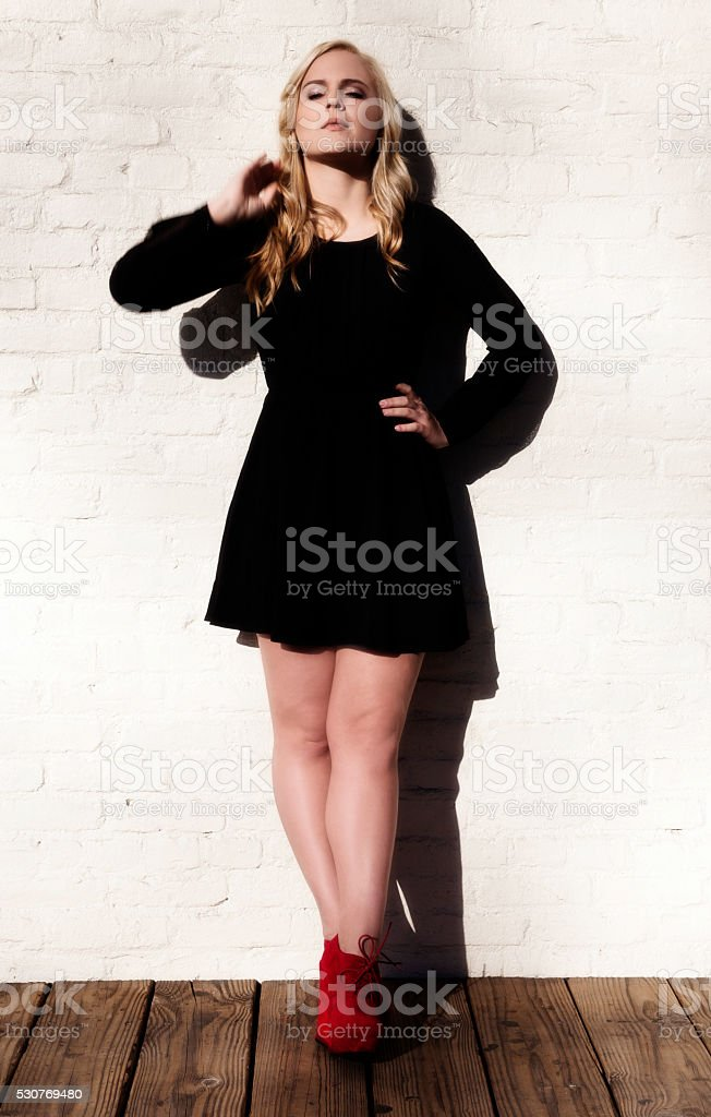 Plump Caucasian Blond Woman Black Dress White Wall stock photo