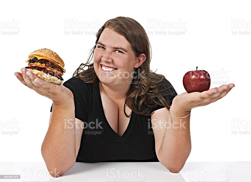 Plump young woman smilingly debates her food choices stock photo