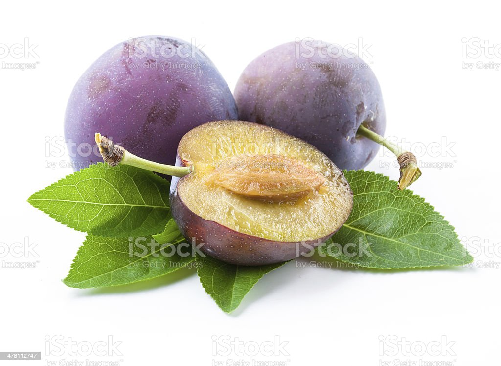 Plums and a half with leaves royalty-free stock photo