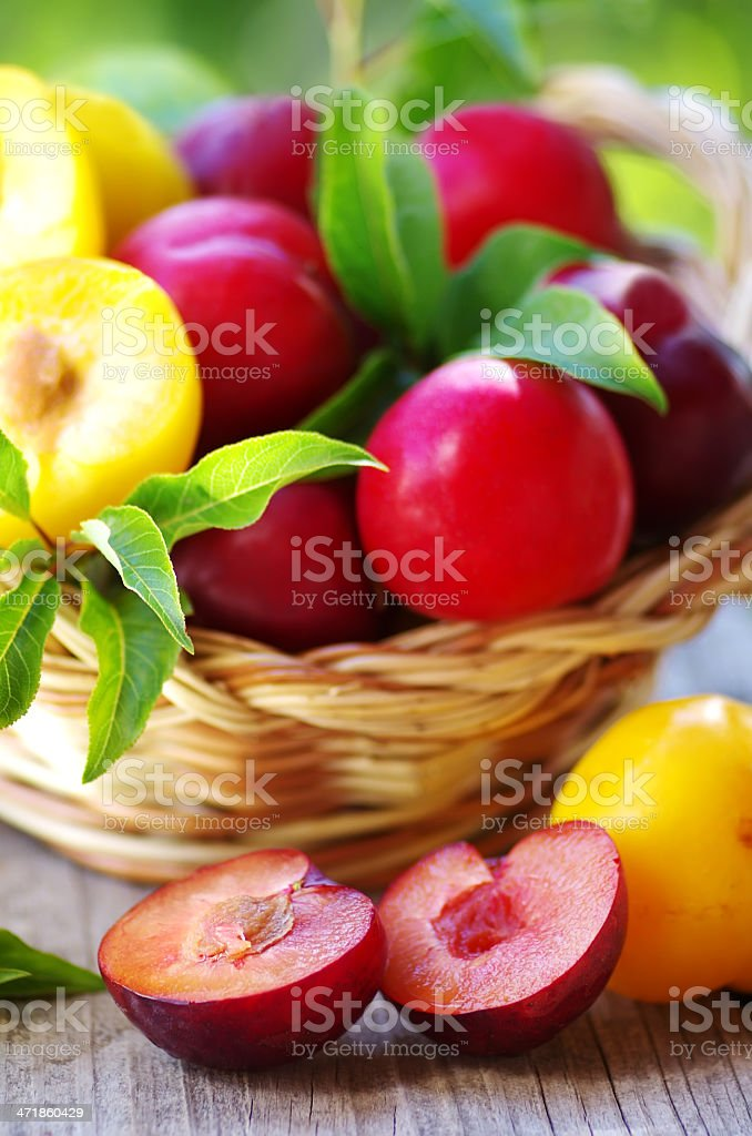 plums in basket and cut plum on table royalty-free stock photo