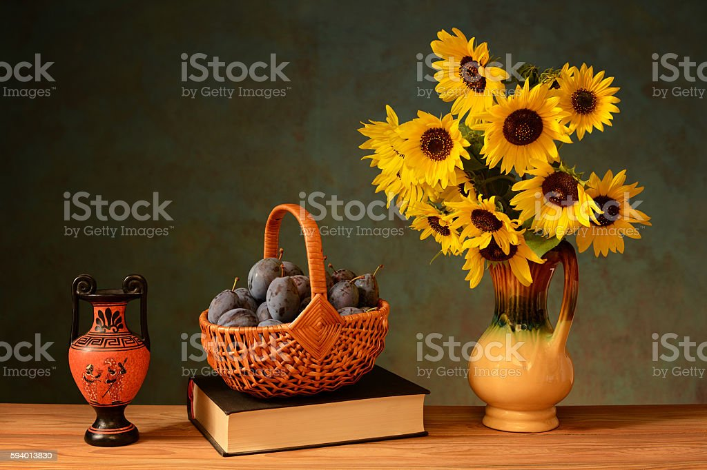 Plums in wicker basket, sunflower, amphorae stock photo
