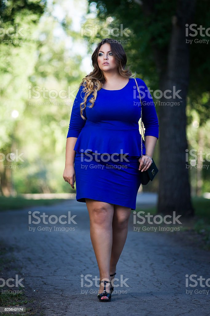 Plus size fashion model in blue dress outdoors, xxl woman stock photo