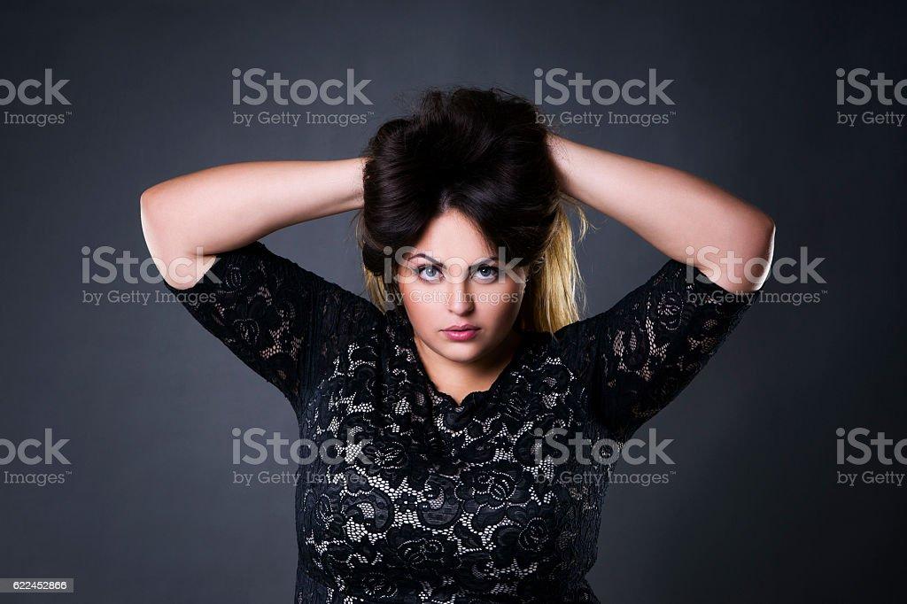 Plus size model in black lace dres, xxl woman portrait stock photo