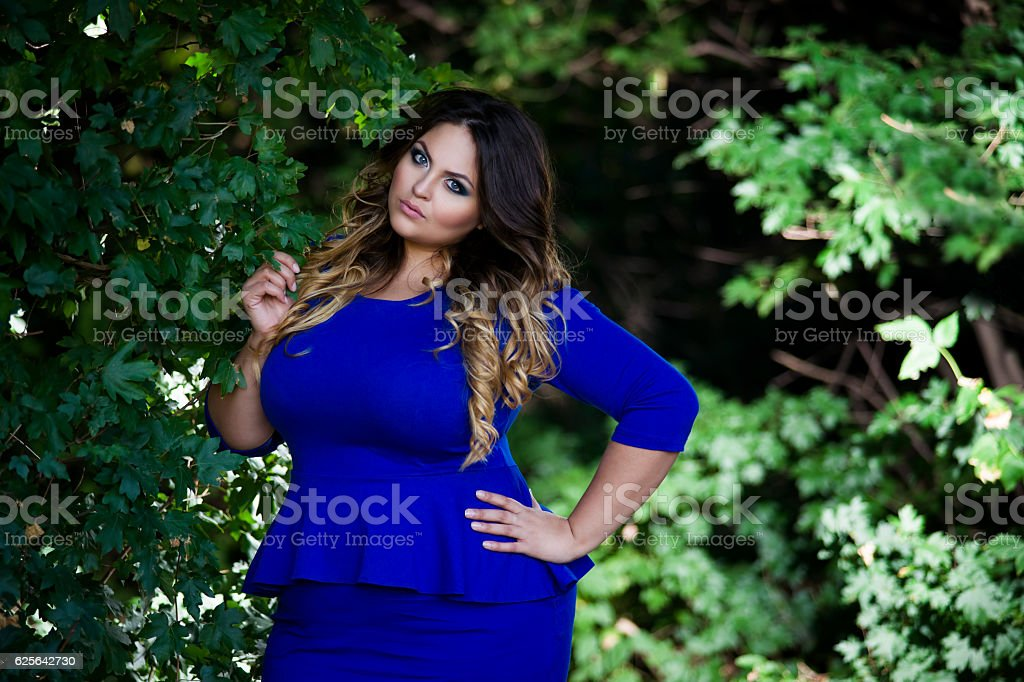 Plus size model in blue dress outdoors, xxl woman stock photo