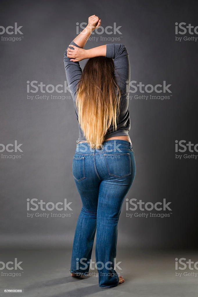 Plus size model in blue jeans, xxl woman on gray stock photo