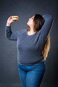 Plus size model posing with hamburger, xxl woman eating burger
