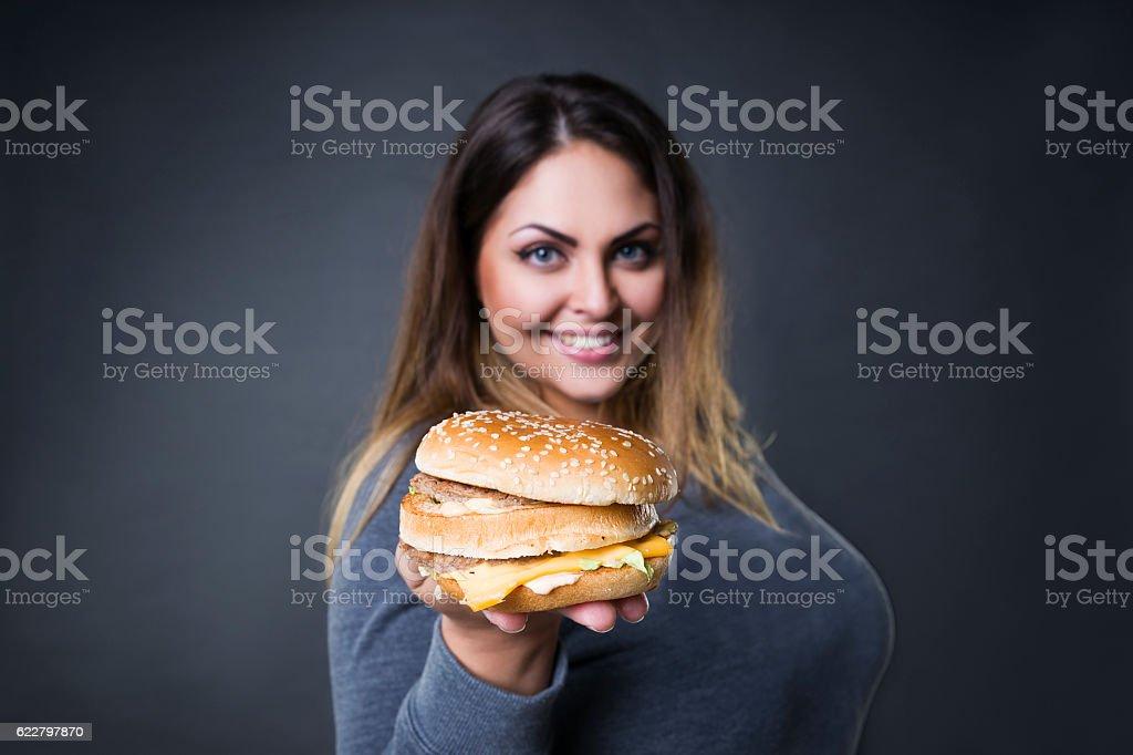 Plus size model posing with hamburger, xxl woman eating burger stock photo